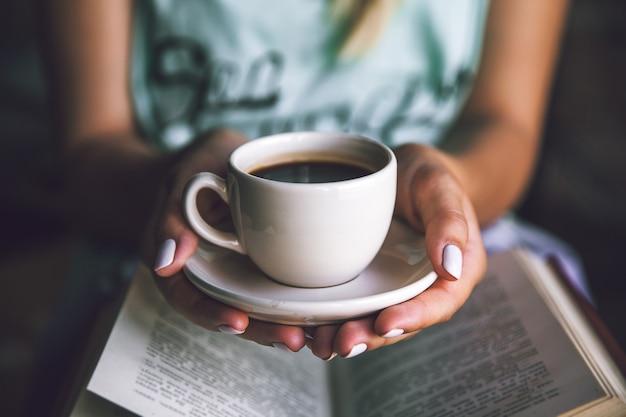 Dziewczyna z filiżanką kawy i książką. budzi się, rano, przerwa, hobby