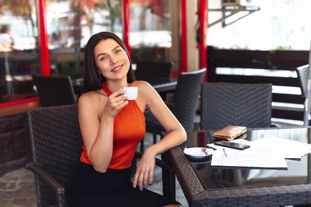 Dziewczyna z filiżanką kawy siedzi w kawiarni. szeroki uśmiech. piękna czysta skóra. biznesowa kobieta po podpisywać dokumenty. spotkanie biznesowe.