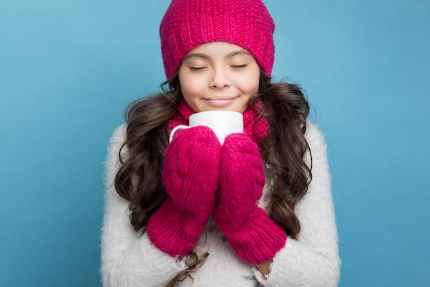 Dziewczyna z filiżanką w rękach na błękitnym tle