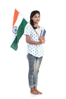 Dziewczyna z flagą indii lub tricolor i książki na białej ścianie, dzień niepodległości indii, dzień republiki indii