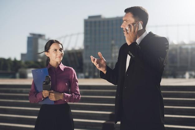 Dziewczyna z folderem i mikrofonem czeka na mężczyznę.