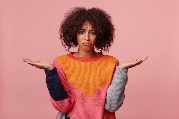 Dziewczyna z fryzurą afro wyglądająca na bezradną urażoną smutną zdenerwowaną, w złym nastroju, stoi z podniesionymi dłońmi, trzymając miejsce na kopię, wydęła usta, czuje beznadziejną niesprawiedliwość, odizolowana na różowo