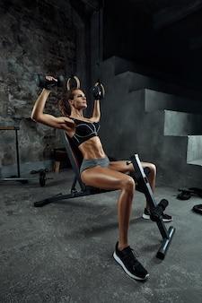 Dziewczyna z hantlami zajmuje się kulturystyką na tle siłowni, kobieta zajmuje się fitnessem z hantlami w sali fitness.