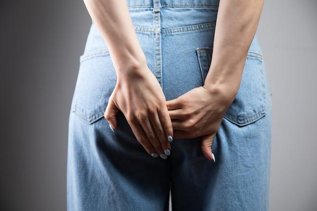 Dziewczyna z hemoroidami trzyma tyłek as