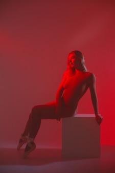 Dziewczyna z idealną szczupłą sylwetką. kobieta pozuje w body w czerwonym świetle w dymie.
