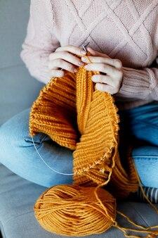 Dziewczyna z igłami robi na drutach sweter