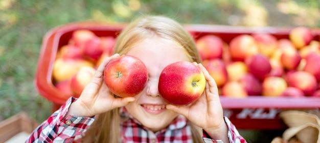 Dziewczyna z jabłkiem w sadzie jabłkowym.