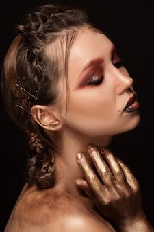 Dziewczyna z jasny makijaż. glamour portret pięknej kobiety z czerwonym makijażem i romantyczną fryzurą. błyszczący, błyszczący rozświetlacz fashion na skórze, seksowne błyszczące usta i ciemne brwi