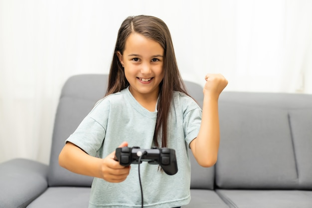 Dziewczyna z joystickiem. podekscytowana dziewczynka grająca w grę wideo i uśmiechnięta