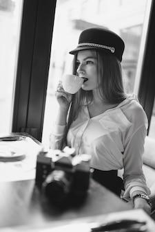 Dziewczyna z kamerą i kawą, czarny i biały