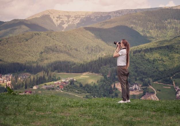 Dziewczyna z kamerą stoi na wzgórzu i fotografuje górę.