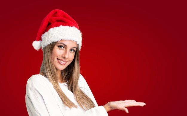 Dziewczyna z kapeluszem na boże narodzenie na izolowanej ścianie wyciągając ręce na bok do zaproszenia