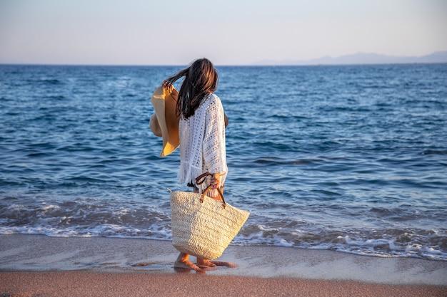 Dziewczyna z kapeluszem w dłoniach i wiklinową torbą spaceruje brzegiem morza. koncepcja wakacji letnich.