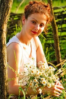 Dziewczyna z kiści rumianku stanąć schludny drewniany płot. portret wsi.
