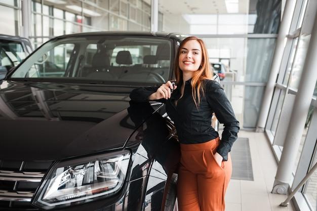 Dziewczyna z kluczem w rękach w pobliżu jej nowego samochodu