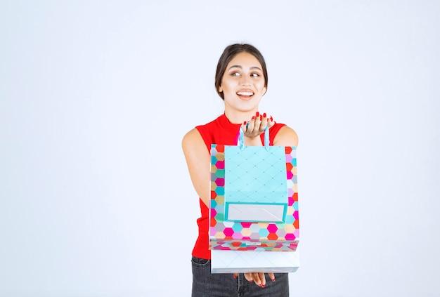 Dziewczyna z kolorowymi torbami na zakupy czuje się pozytywnie.