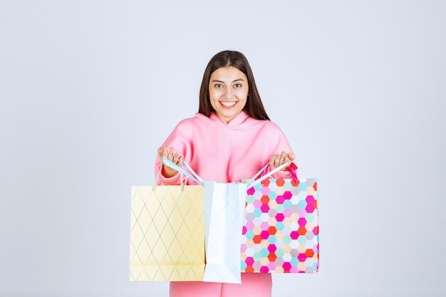 Dziewczyna z kolorowymi torbami na zakupy, otwierając je i sprawdzając.