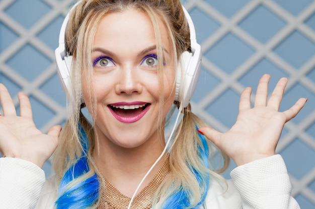 Dziewczyna z kolorowymi włosami i dużymi słuchawkami.