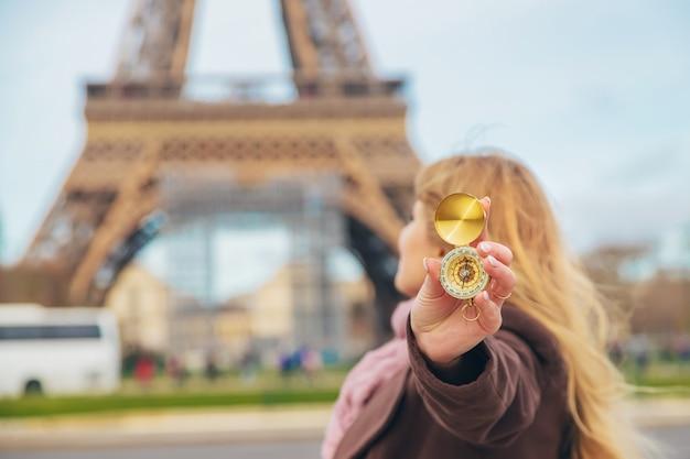 Dziewczyna z kompasem w rękach w pobliżu wieży eiffla w paryżu. selektywne ustawianie ostrości.