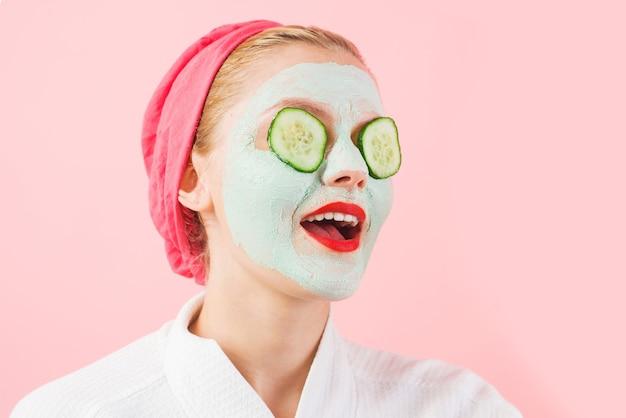 Dziewczyna z kosmetyczną maską na twarzy. plasterki ogórka na oko. maska na twarz. zabieg upiększający. terapia uzdrowiskowa.