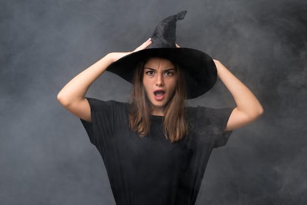 Dziewczyna z kostium wiedźmy na imprezy halloween na pojedyncze ciemne ściany z niespodzianką wyraz twarzy