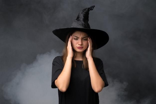 Dziewczyna z kostiumem wiedźmy na halloween na izolowanych ciemnych ścianach niezadowolona i sfrustrowana czymś. negatywny wyraz twarzy