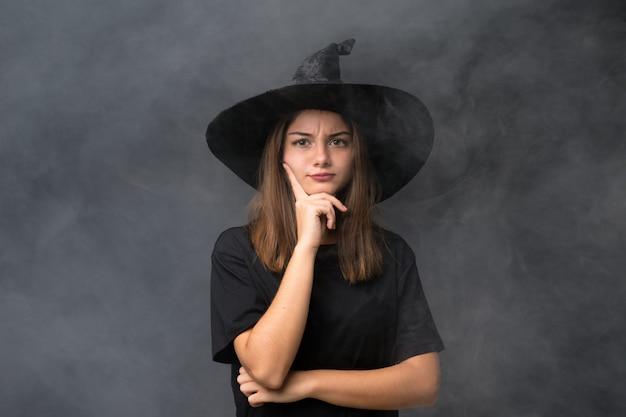 Dziewczyna z kostiumem wiedźmy na imprezy halloween na pojedyncze ciemne ściany myśląc pomysł