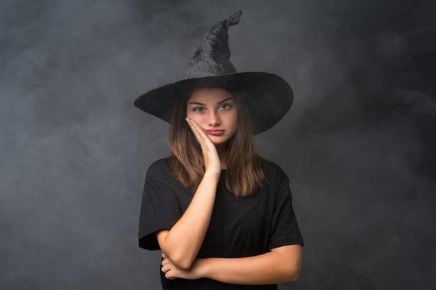 Dziewczyna z kostiumem wiedźmy na imprezy halloween na pojedyncze ciemne ściany niezadowolony i sfrustrowany