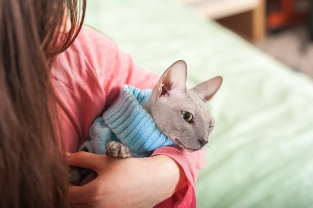 Dziewczyna z kotem w sypialni na łóżku. zwierzęta i ludzie.