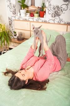 Dziewczyna z kotem w sypialni na łóżku.