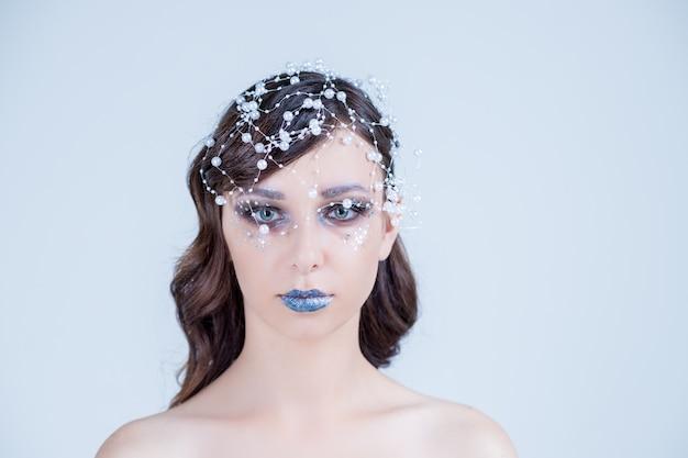 Dziewczyna z kreatywnym makijażem na nowy rok. portret zimowy jasne kolory, niebieskie usta, eleganckie włosy z kryształami, koralikami i klejnotami. twoja sztuka. królowa śniegu.