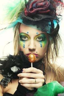 Dziewczyna z kreatywnym makijażem trzyma lizaka. styl lalki. ścieśniać