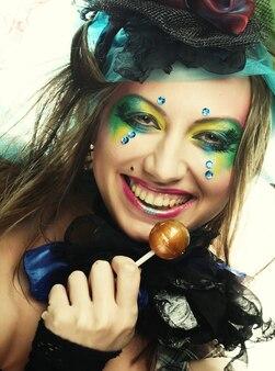 Dziewczyna z kreatywnym makijażem trzyma lizaka. styl lalki.