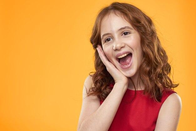 Dziewczyna z kręcone włosy czerwona sukienka zabawa dzieciństwo emocje żółty.