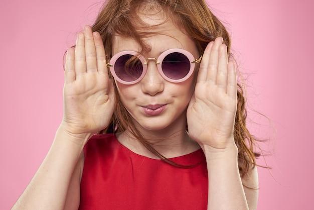 Dziewczyna z kręconych włosów ciemne okrągłe okulary zabawa czerwona sukienka różowym tle