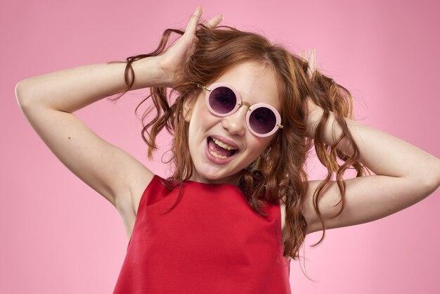 Dziewczyna z kręconymi włosami ciemne okrągłe okulary zabawa czerwona sukienka różowy
