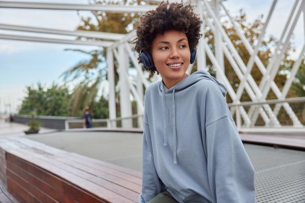 Dziewczyna z kręconymi włosami odwraca wzrok szczęśliwie ubrana w luźną bluzę z kapturem słucha ścieżki dźwiękowej przez bezprzewodowe słuchawki odpoczywa po długiej podróży pozuje na zewnątrz