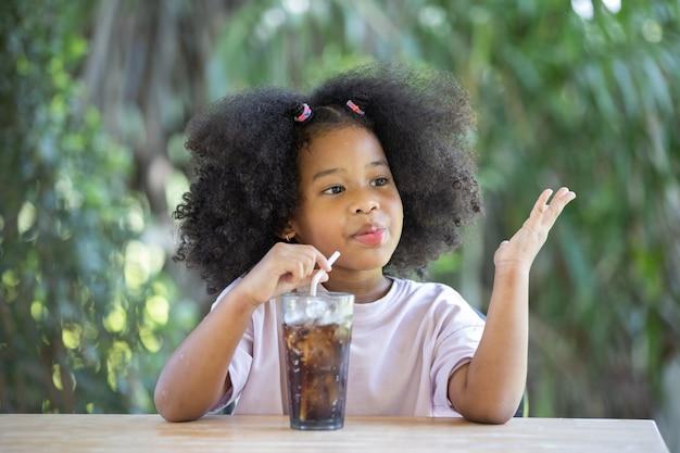 Dziewczyna z kręconymi włosami piła napój bezalkoholowy