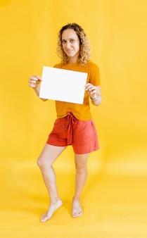 Dziewczyna z kręconymi włosami trzyma pustą kartę. samodzielnie na żółtym tle uśmiechnięta portret kobiety.