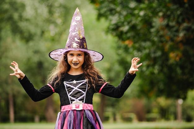 Dziewczyna z kręconymi włosami w stroju czarownicy na halloween