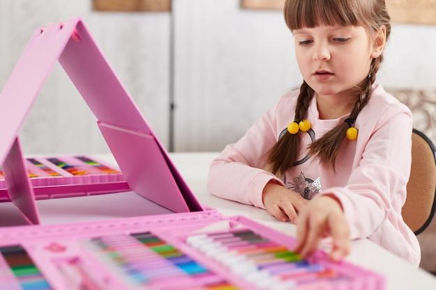 Dziewczyna z kredkami woskowymi rysuje obraz siedząc przy stole