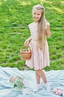Dziewczyna z królikiem i jajkami na wielkanoc w parku na zielonej trawie