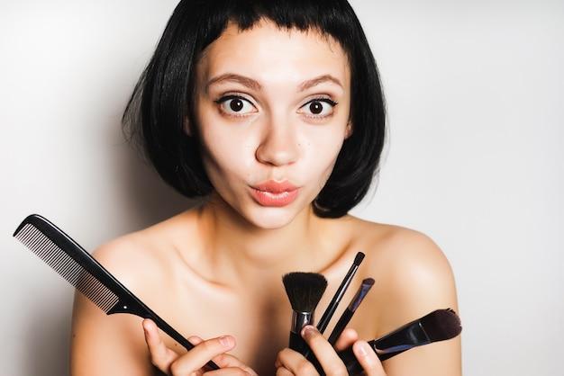 Dziewczyna z krótkimi czarnymi włosami trzyma w dłoniach pędzle do makijażu i zastanawia się, który pędzel zacząć malować