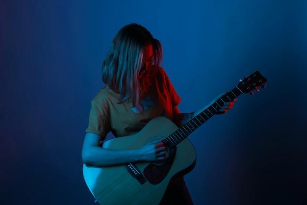 Dziewczyna z krótkimi włosami cieszy się gitarą w niebieskim i czerwonym świetle.