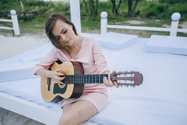 Dziewczyna z krzywym głowy podczas gry na gitarze