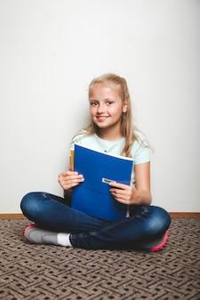Dziewczyna z książek wykonywania na podłodze