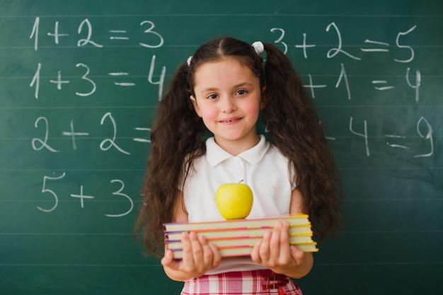 Dziewczyna z książkami i jabłko w klasie