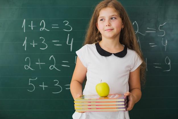 Dziewczyna z książkami w klasie matematyki