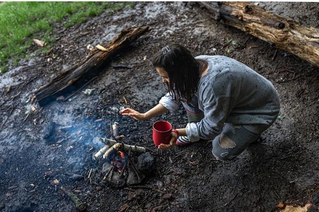 Dziewczyna z kubkiem w dłoni rozpala ogień, żeby się ogrzać.