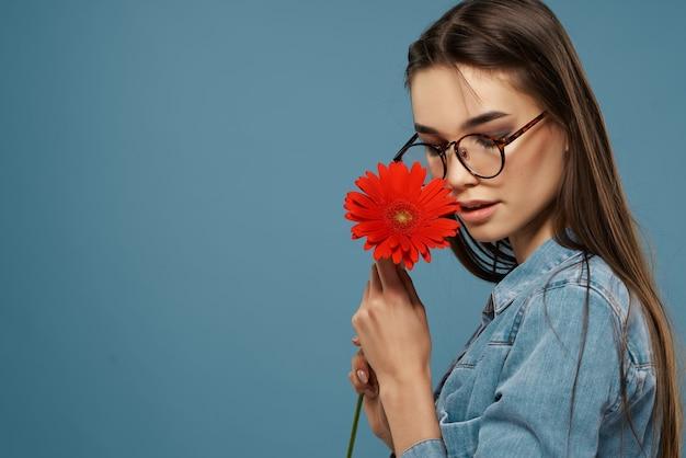 Dziewczyna z kwiatem w pobliżu jej twarzy okulary zbliżenie glamour